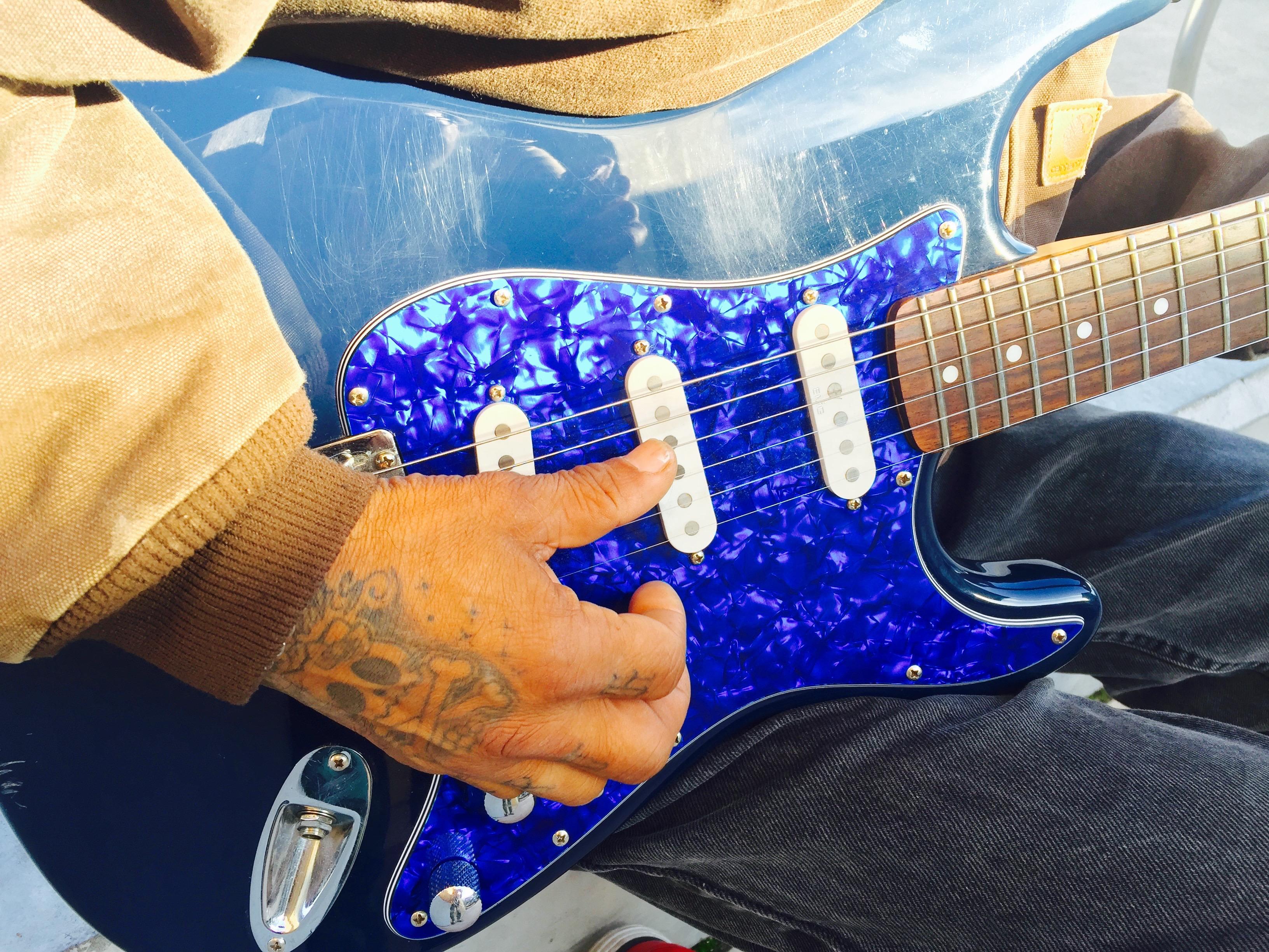 Kai Lani strums the guitar